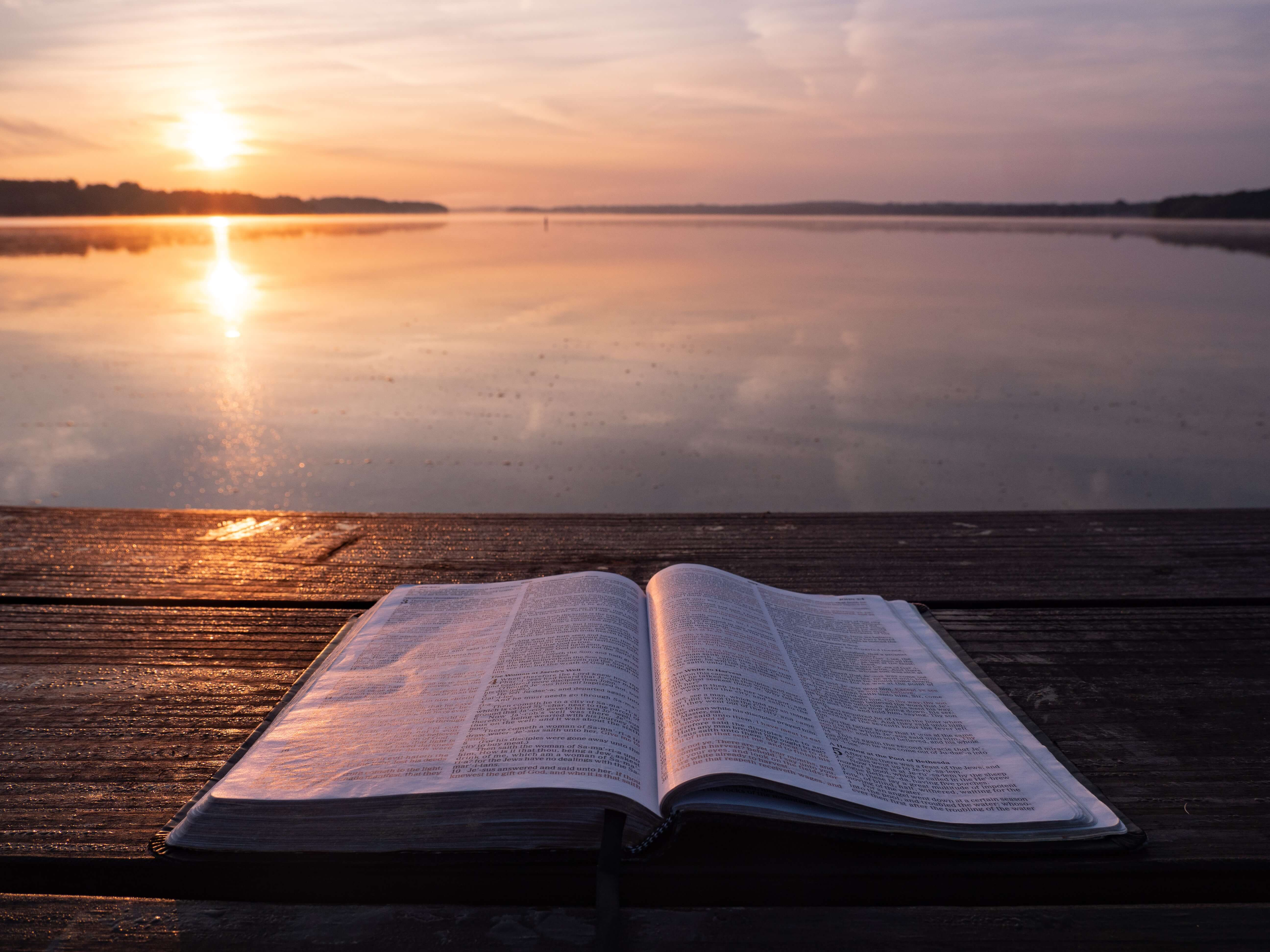 open bible in front of a lake