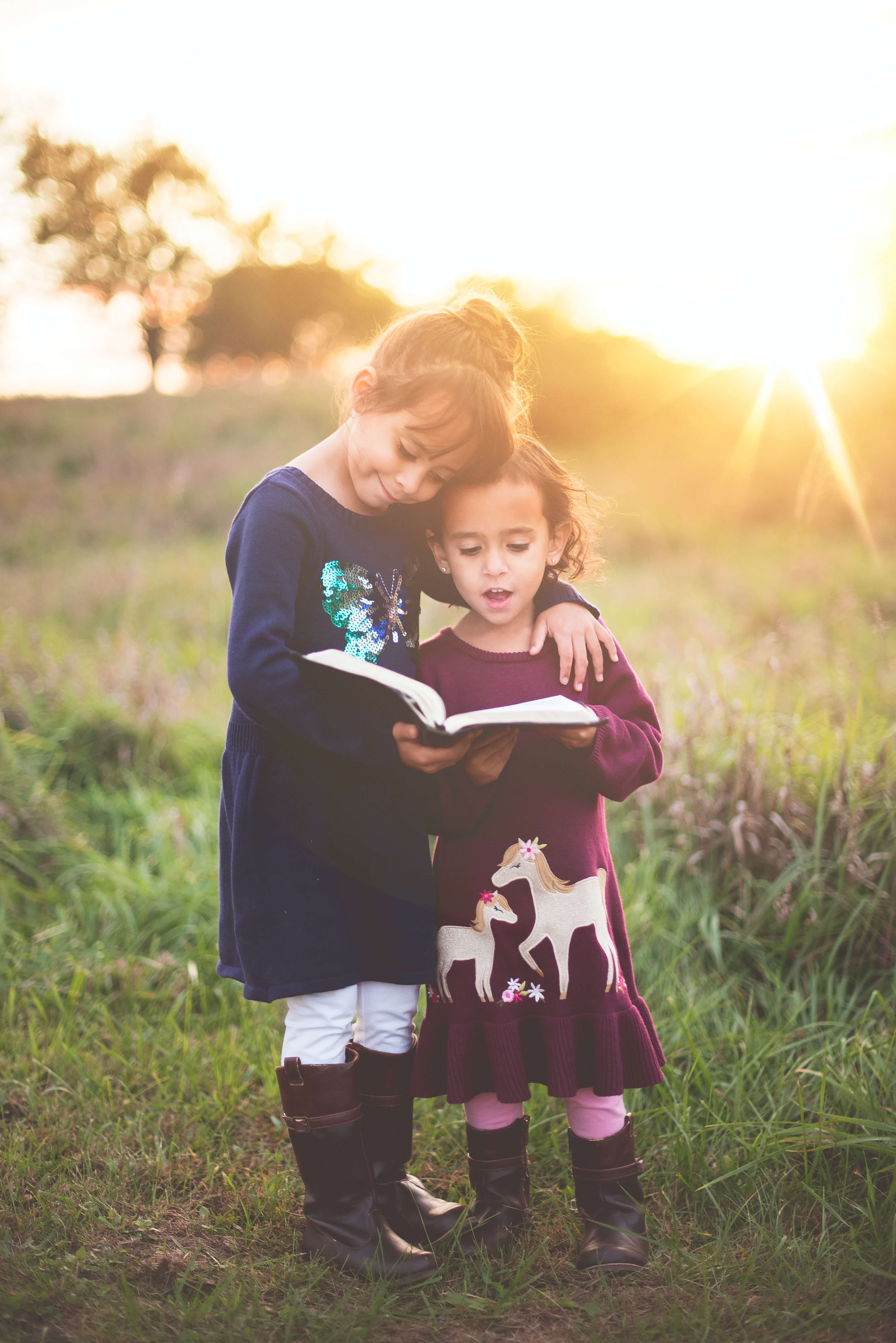 Children reading a book at golden hour